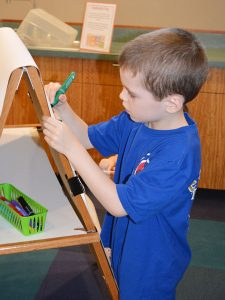 child writing on easel