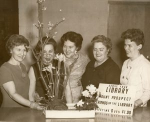 Friends of the Library--Four women with floral display and sign, 1966