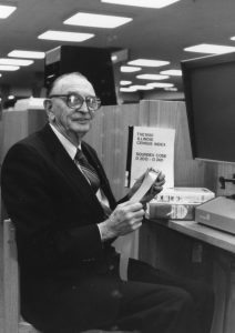 Harold Weary in genealogy room, sitting at microfilm machine, c1980