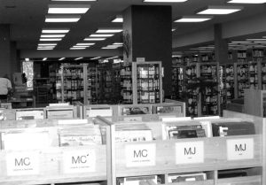 Interior black and white view of the library main floor showing the video and record collection c1987