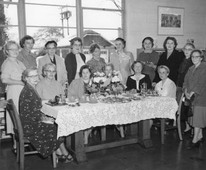 Ladies around table for Library anniversary party 1955