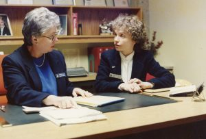 Patricia Kelly and Marilyn Genther sitting and talking in office c1990
