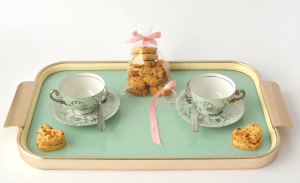 teacups and heart-shaped cookies on a mint-colored tray