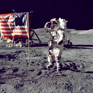 Man walking on the moon next to U.S. flag