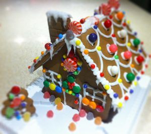 gingerbread house with a chimney and covered in icing and candy decorations