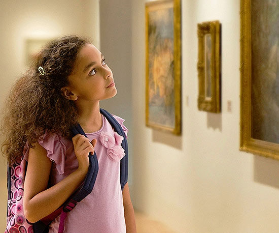 girl with backpack looking at paintings in an art museum