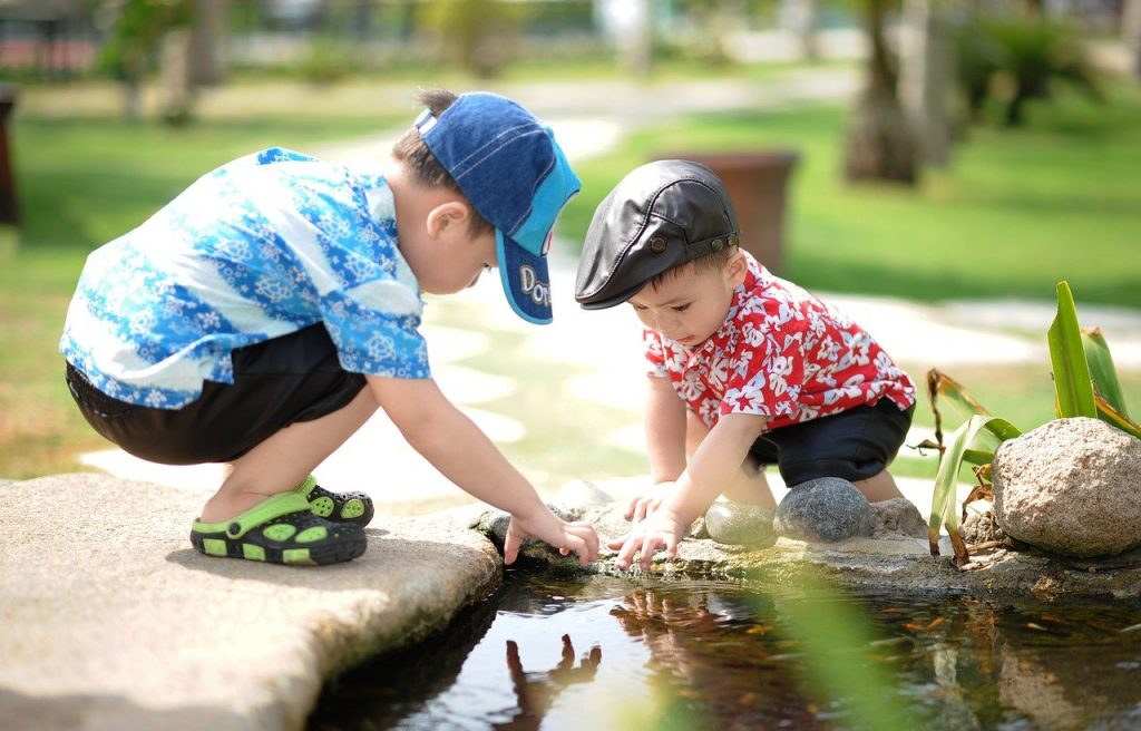 two little boys reaching into a pond in a park